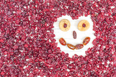 Funny face made of dried fruits on white wooden background Royalty Free Stock Images