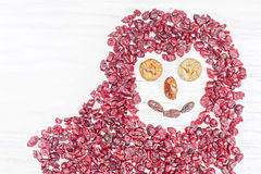 Funny face made of dried fruits on white wooden background Stock Photo
