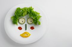 Funny face made with vegetables. Funny face made with salad, cucumber, pepper, pepperoni, courgette, paprika and mais Royalty Free Stock Photography