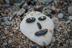 Funny face from marine rocks on the shore Stock Photo