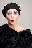 Funny face of mature woman in fur on gray. Mature brunette with glamour makeup in black fur, with black beret ,funny face Stock Photos