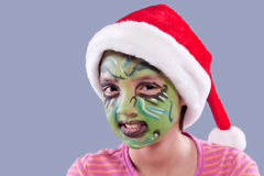 Funny face paint and Santa hat. A young girl  wears a Santa hat and has face paint similar to the Grinch Royalty Free Stock Photography