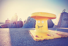 Funny face painted on a mooring bollard, vintage style. Stock Photos