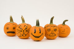 Funny Face Pumpkins. A set of bright orange mini-pumpkins with funny faces drawn on them Stock Images