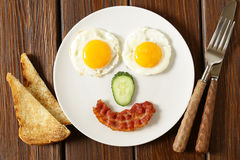 Funny face serving breakfast, fried egg. And toast Royalty Free Stock Photos
