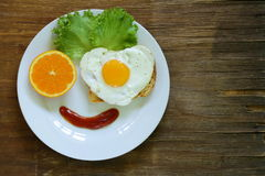 Funny face serving breakfast, fried egg, toast Royalty Free Stock Images