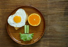 Funny face serving breakfast, fried egg, toast Stock Image