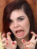 Stressed Teen. A funny faced teenage girl making a grrr and claw motion with long dark hair and yellow blouse against a rustic red background. Goofing around Stock Photo