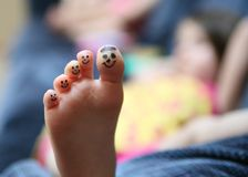 Funny face toes. Bored little lying on couch girl showing the bottom of her foot with smiley faces drawn on her toes Stock Image