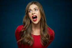 Funny face woman portrait on blue background. Red dress. Long curly hair Stock Image