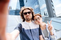 Young woman wearing glasses making funny face for selfie. Funny face. Young good-looking women wearing glasses making funny face for selfie with her boyfriend royalty free stock images