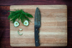 Funny faces of cucumber slices and dill on the chopping board wi. Th a knife, top view Royalty Free Stock Images