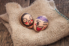 Funny faces drawn on eggs on sack cloth stock photography