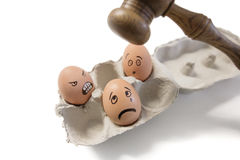Funny faces on egg with gavel about to hit Stock Photography