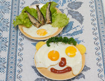 Funny faces from eggs with cheese and sauce Royalty Free Stock Photos