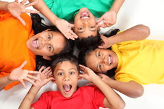 Funny faces by four happy school friends together. Four happy young school friends having fun together. Kids are lying on the floor together looking up at the Stock Photography