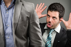 Funny faces. Image of a male professional making faces behind someone's back Stock Images