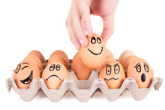 Funny faces painted on brown eggs in a tray Royalty Free Stock Photos