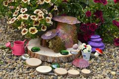 Funny Fairy Dollhouse On Wooden Planks By Flowerbed With Petunia Flowers In The Garden Stock Photos