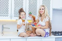 Funny family on the background of bright kitchen. Mother and her daughter girl are having fun with colorful donuts. Dieting concept and junk food. Yellow, pink Stock Images