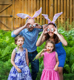 Funny Family Easter Portrait. A funny family portrait on Easter of a mother and father wearing bunny ears and holding up silly eyes made from eggs as their Royalty Free Stock Images