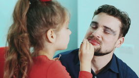Funny family. Father and his child daughter girl paints lips and eyes to her father. Close-up view. stock video