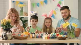 Funny family with kids wearing bunny ears painting eggs on Easter day stock footage