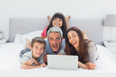 Funny family lying on bed using their laptop Stock Photography