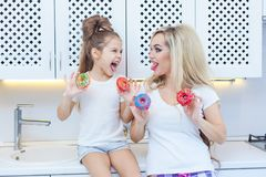 Free Funny Family On The Background Of Bright Kitchen. Mother And Her Daughter Girl Are Having Fun With Colorful Donuts Stock Photo - 107435400