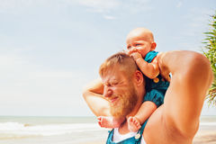 Funny family photo. Baby son sit on father shoulders. Funny face portrait of happy family - baby son sit on father shoulders, walk with fun along sea surf on Stock Photo