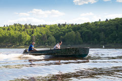 Funny family riding hand motorboat. In lake stock photo