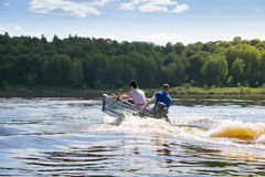 Funny family riding hand motorboat. In lake royalty free stock photo