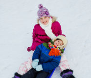 Funny family is sledging in winter-landscape Royalty Free Stock Image