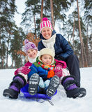 Funny family is sledging in winter-landscape Royalty Free Stock Photo