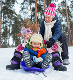 Funny family is sledging in winter-landscape Stock Image