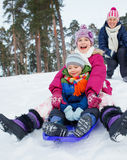 Funny family is sledging in winter-landscape Royalty Free Stock Photos