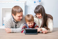 Funny family using the tablet near Christmas tree. Royalty Free Stock Photos