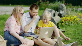 Funny family video chat. Family of father, mother and son lough a lot having Video chat using laptop on summer picnic stock video footage