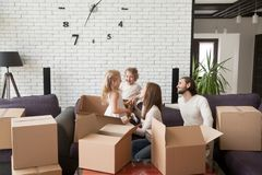 Happy family with children in living room. Funny family, young first time buyers in living room. Parents sitting on couch playing with kids, people surrounded by stock photos