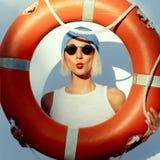 Funny fashion blonde on wall background with orange lifebuoy Stock Images