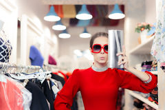 Funny fashion woman in red dress with big glasses and shinny bag. Cute lady in red glamour stylish party gown Royalty Free Stock Photography