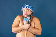 Funny fat man in blue cap sing in the shower. Fun and cleanliness royalty free stock images