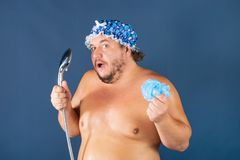 Funny fat man in blue cap sing in the shower. Fun and cleanliness stock photography