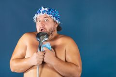 Funny fat man in blue cap sing in the shower. Fun and cleanliness stock images
