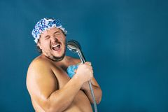Funny fat man in blue cap sing in the shower. Fun and cleanliness royalty free stock photo