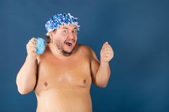 Funny fat man in blue cap sing in the shower. Funny fat man in blue cap and with sponge in the shower. Fun and cleanliness royalty free stock image