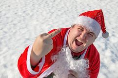 Funny fat man dressed as santa claus is sitting on the snow. Frosty winter and sunny day stock photography