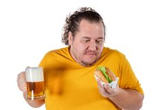 Funny fat man eating burger and drinking alcohol beverage on white background. Funny fat man eating burger and drinking alcohol beverage stock image