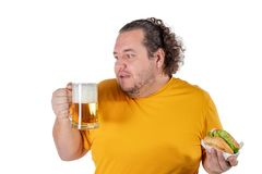Funny fat man eating burger and drinking alcohol beverage on white background. Funny fat man eating burger and drinking alcohol beverage royalty free stock image
