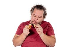 Funny fat man eating small croissant on white background. Good morning and breakfast royalty free stock photos